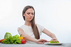 Cheerful young girl is choosing between healthy and harmful food